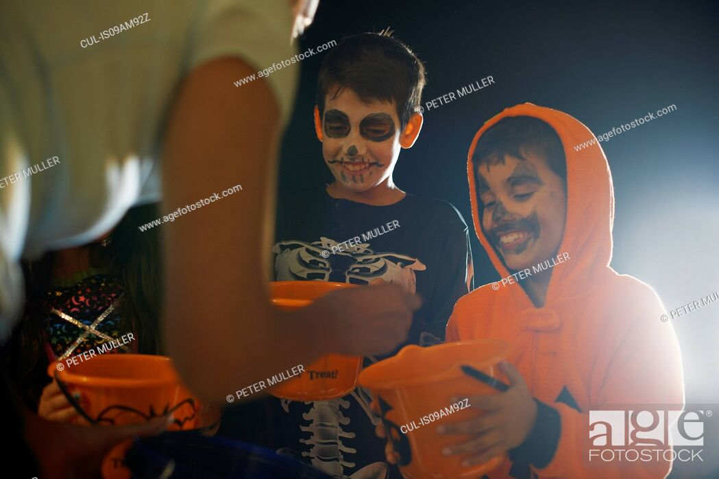 Imagen: Three children wearing halloween costumes trick or treating.
