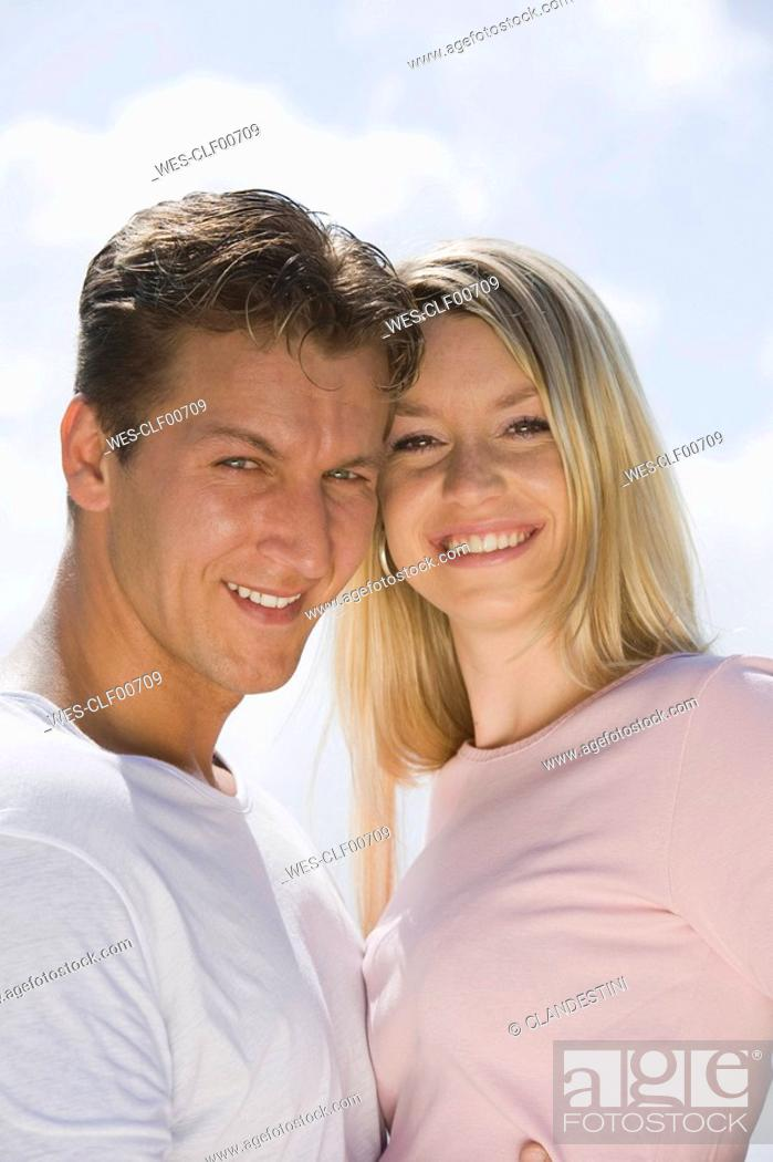 Stock Photo: Germany, Bavaria, Munich, Young couple head to head, smiling, portrait, close-up.