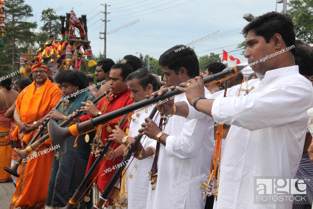 Stock Photo - CANADA, SCARBOROUGH, 27.07.2013, Tamil Hindu musicians play  the nadaswaram (a long wooden pipe) as they escort a large chariot  containing an ...