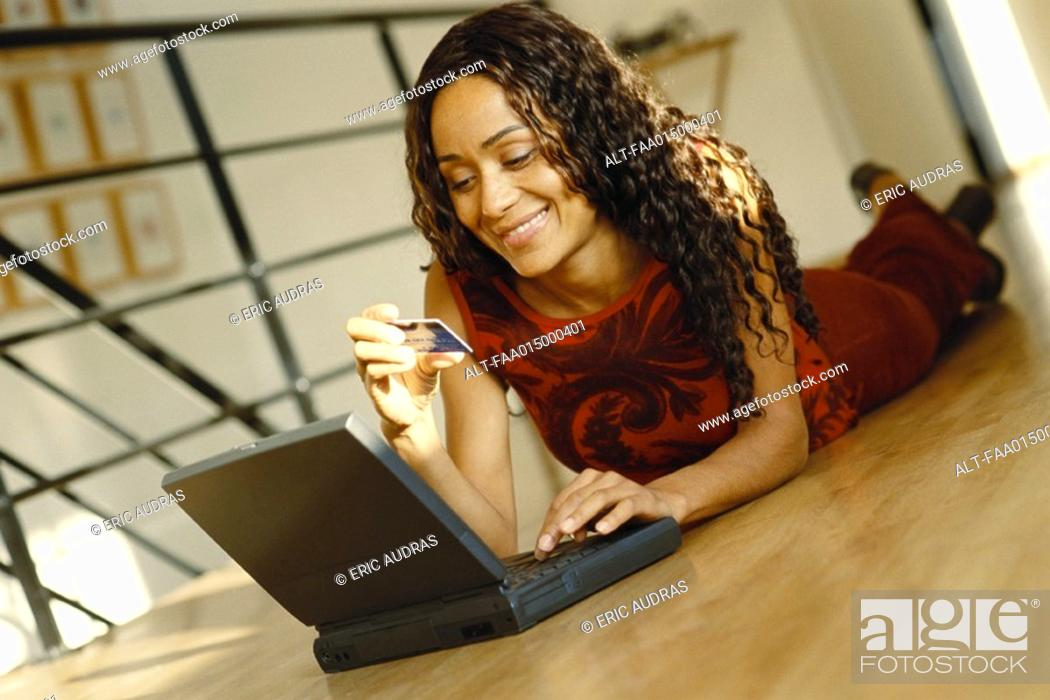 Stock Photo: Young woman lying on ground with laptop, holding up credit card.