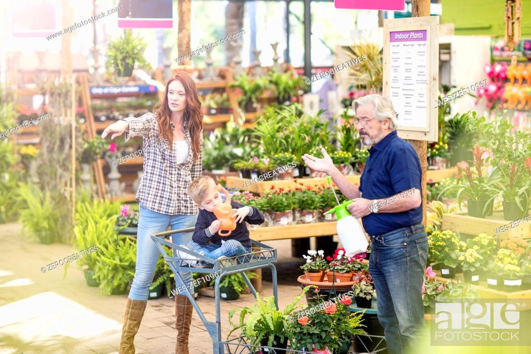 Stock Photo: Gardener helping clients at garden centre.