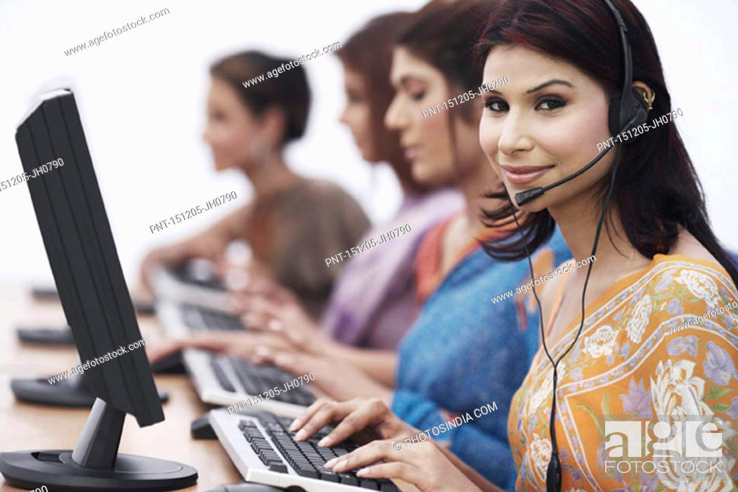 Stock Photo: Close-up of four businesswomen sitting in front of computers.
