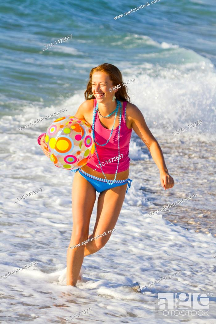 Stock Photo: Attractive young woman with an inflatable ball on the beach.
