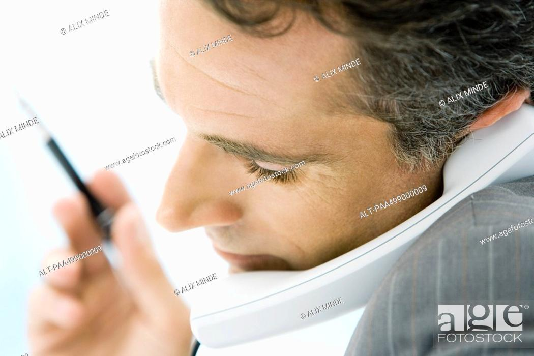 Stock Photo: Man holding phone between chin and shoulder, side view, close-up.