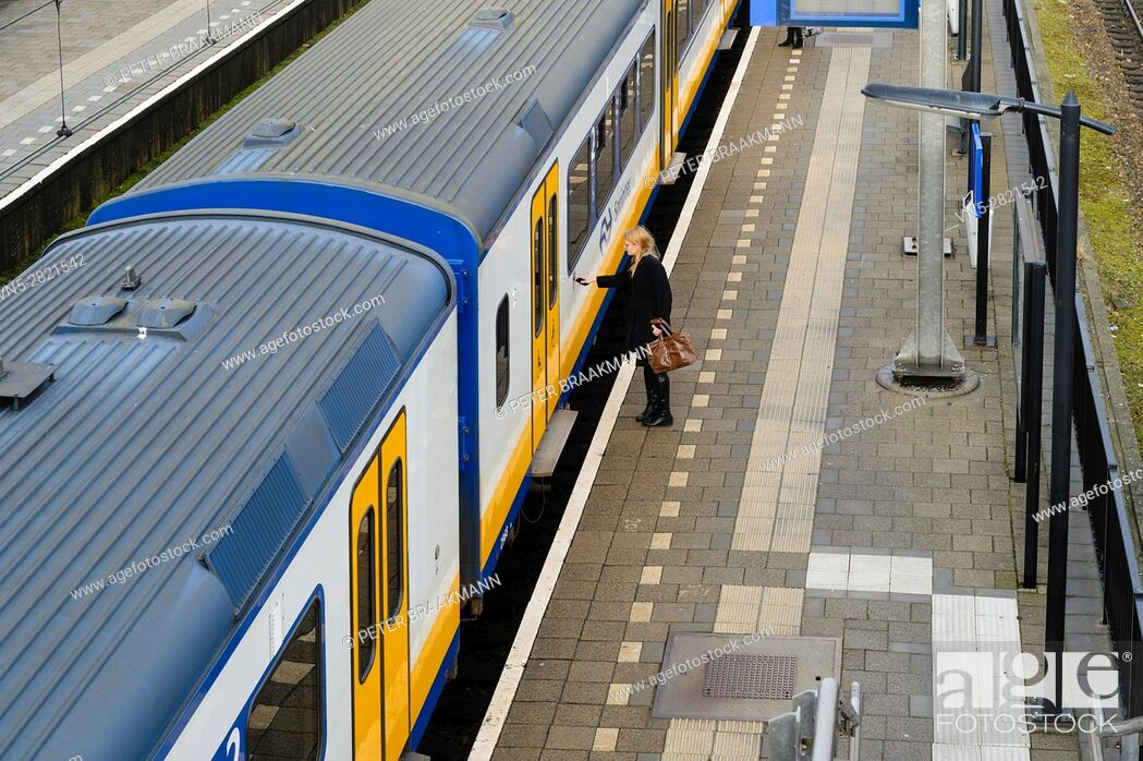 """Stock Photo: LAGE ZWALUWE, THE NETHERLANDS â. """" JANUARY 29: Passenger train rides inside station to let passengers in and out on January 29, 2017."""