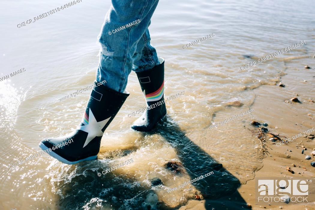 Stock Photo: kids rain boots walking through the sea on a sunny day in England.