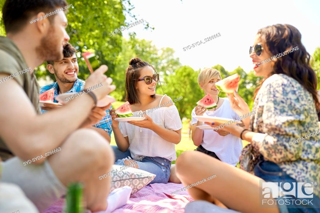 Stock Photo: happy friends eating watermelon at summer picnic.