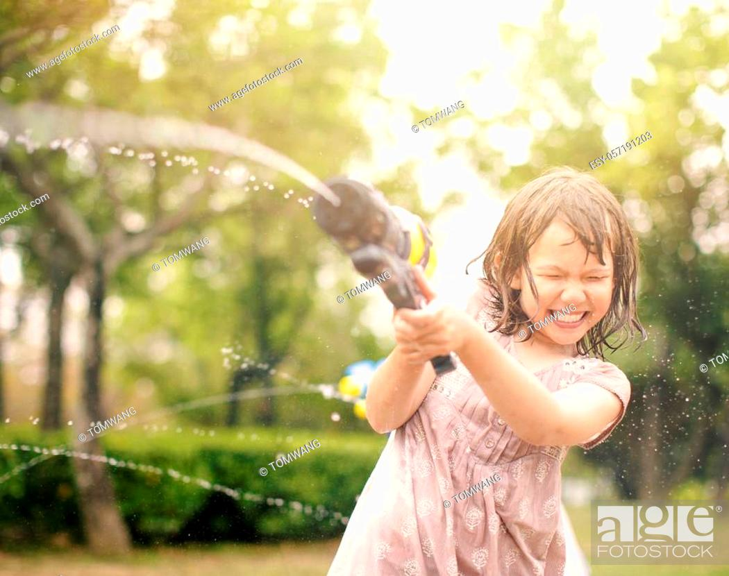 Imagen: happy little girls playing with water guns on summer.