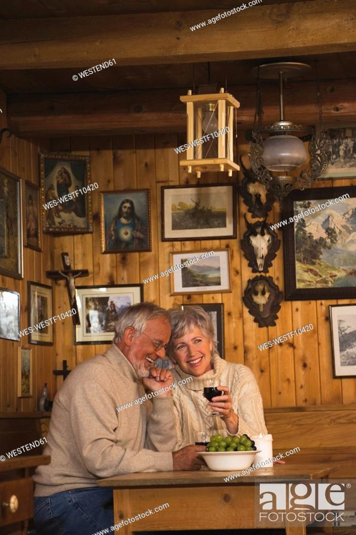 Stock Photo: Senior couple sitting at table in Log Cabin.