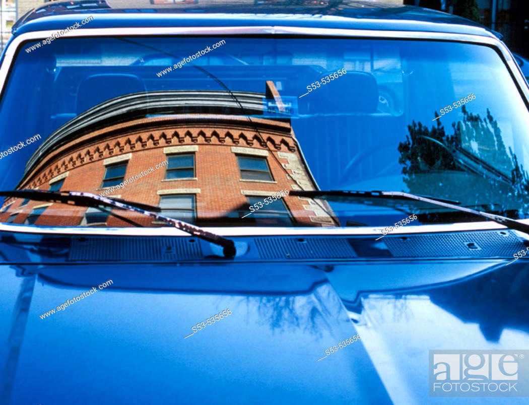 Stock Photo: Brick building reflected in windshield in blue car.