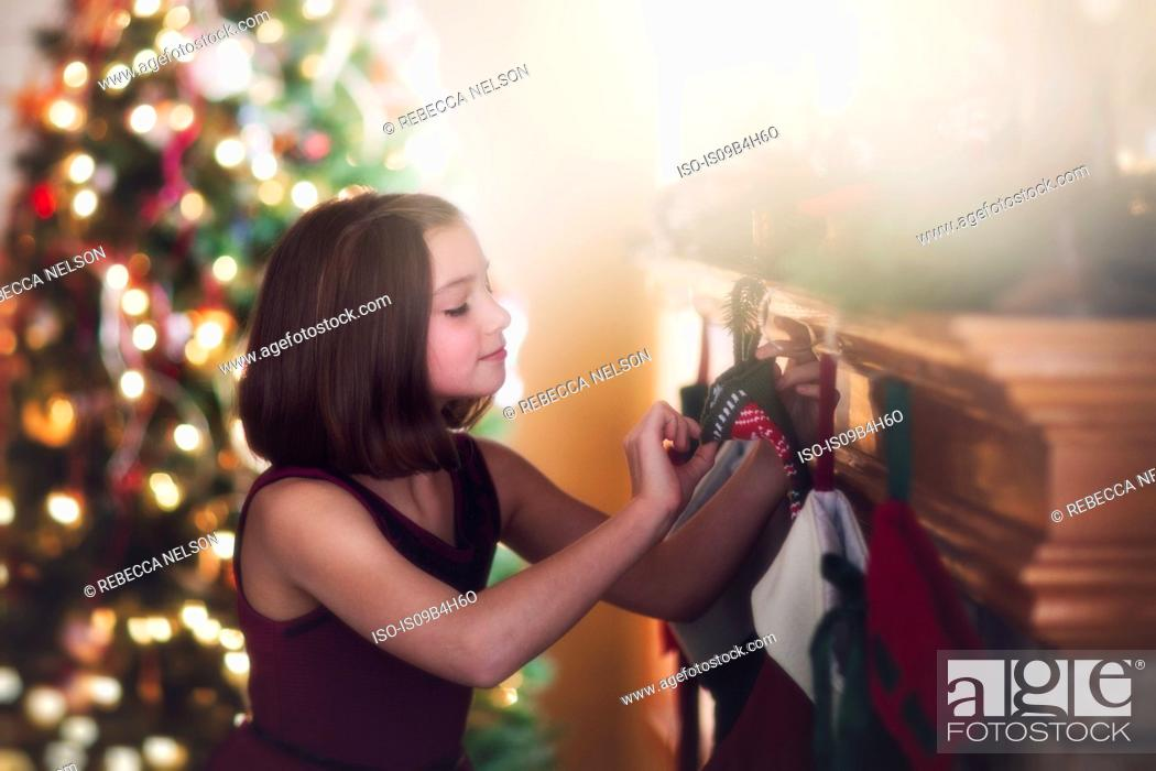Stock Photo: Young girl looking at christmas stocking.