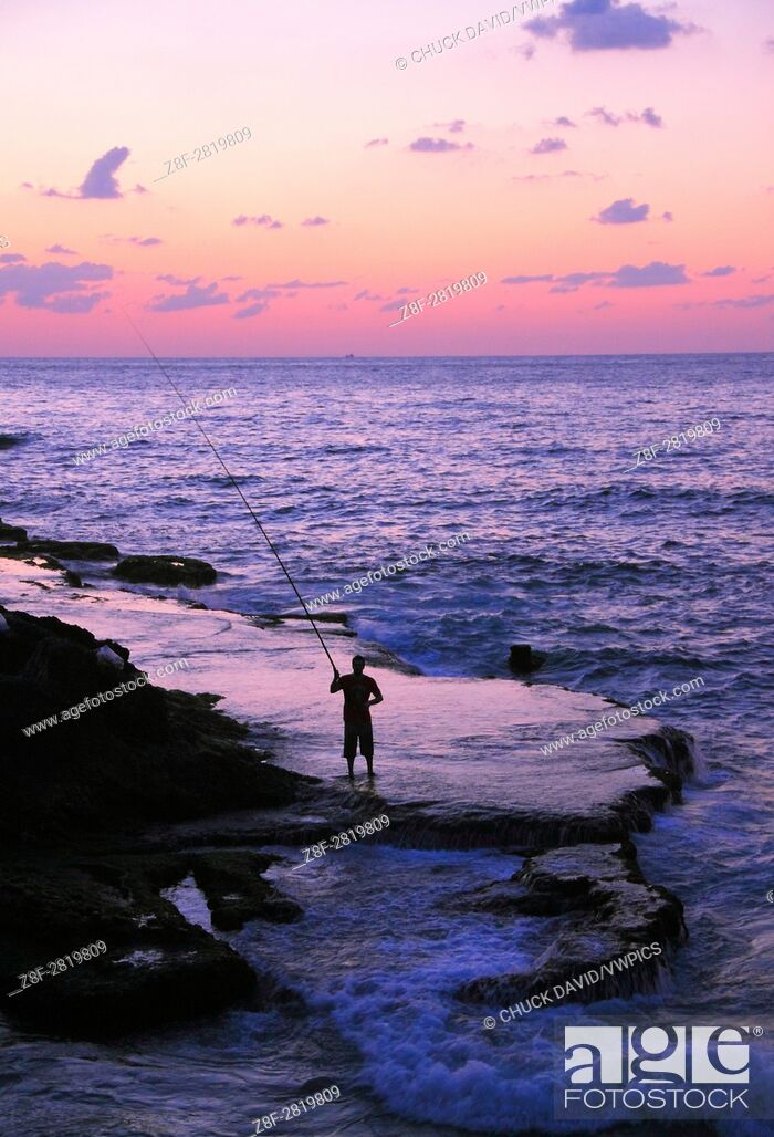 Stock Photo: A lone fisherman casts his rod along Beirut's rocky Mediterranean shoreline at sunset, Lebanon.