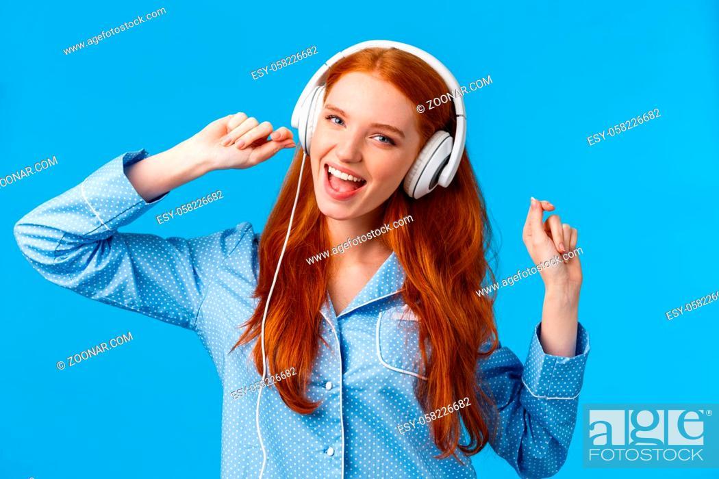 Stock Photo: Girl waking up starting day with music. Joyful carefree redhead teenager dancing in nightwear, raising hands up wearing large white headphones singing along.