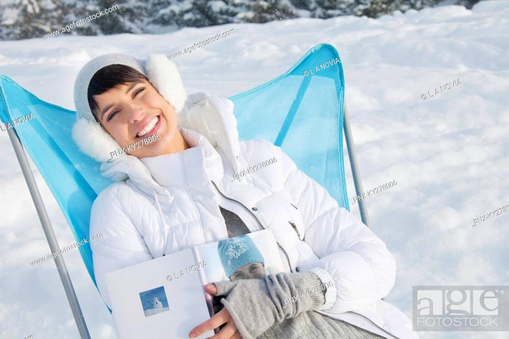 Stock Photo: Young woman resting in snow, smiling at camera.