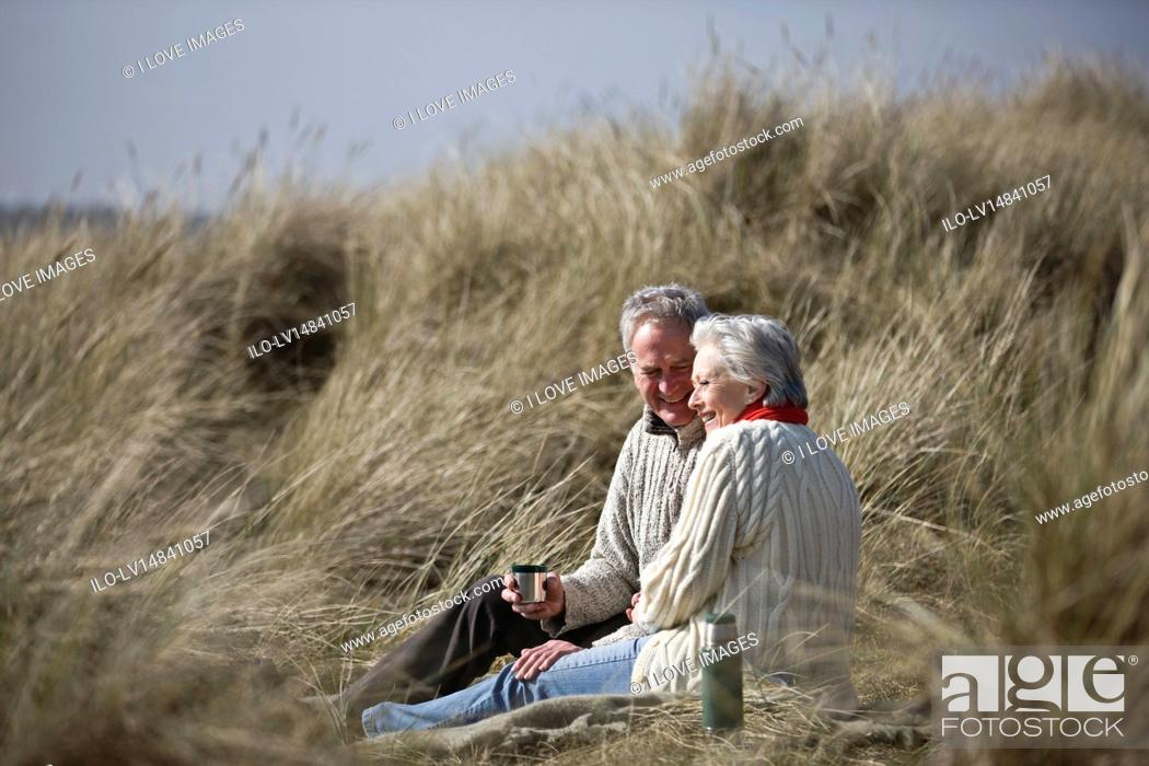 Stock Photo: A senior couple sitting amongst the sand dunes, drinking a hot beverage.