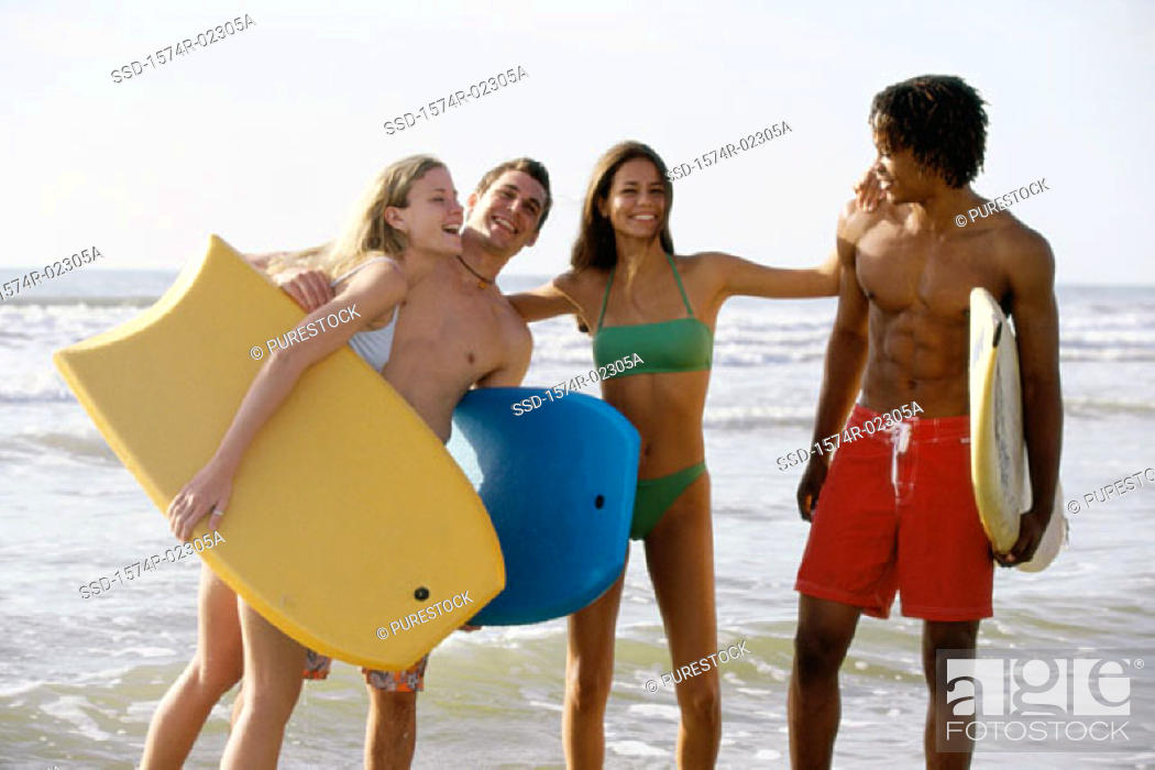 Stock Photo: Two teenage couples standing on the beach holding boogie boards.