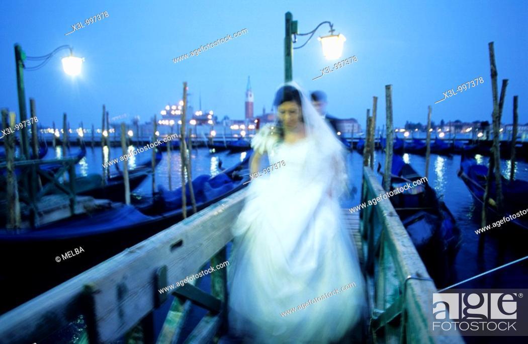 Stock Photo: Bride and groom with gondolas at San Marco Pier and San Giorgio Maggiore in background  Venice  Veneto, Italy.