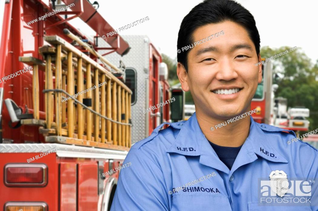 Stock Photo: Asian firefighter next to fire truck.