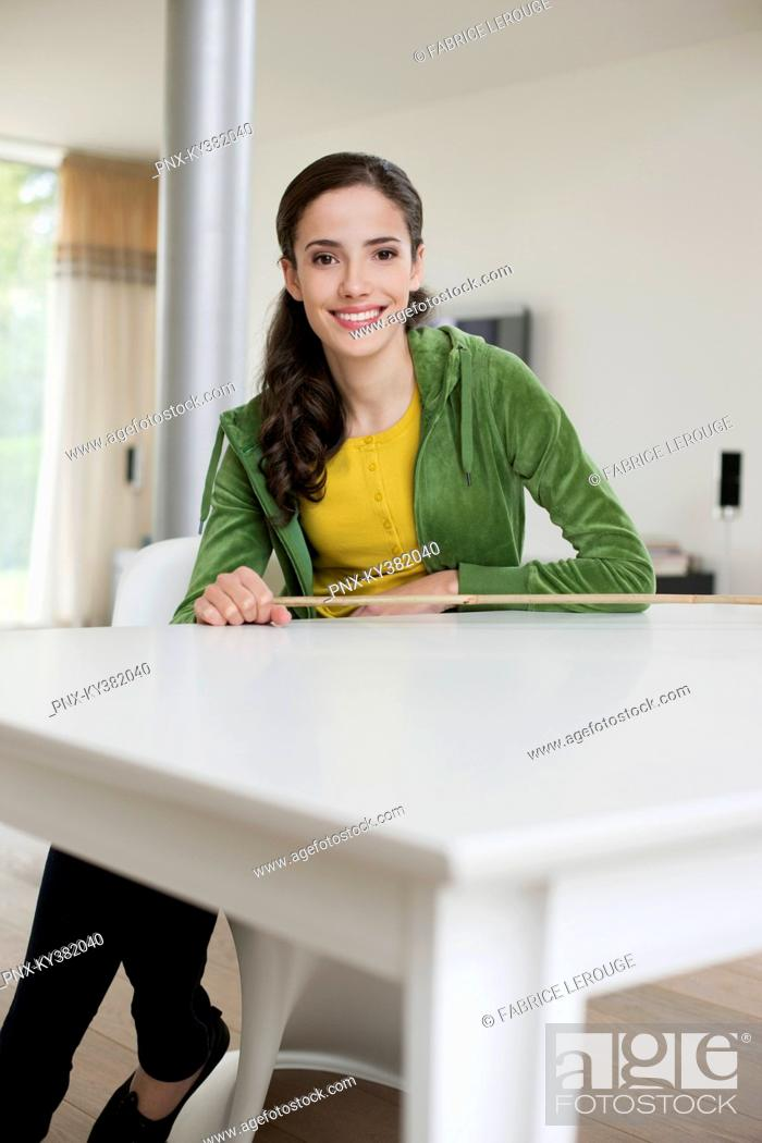 Stock Photo: Happy woman sitting at a table.