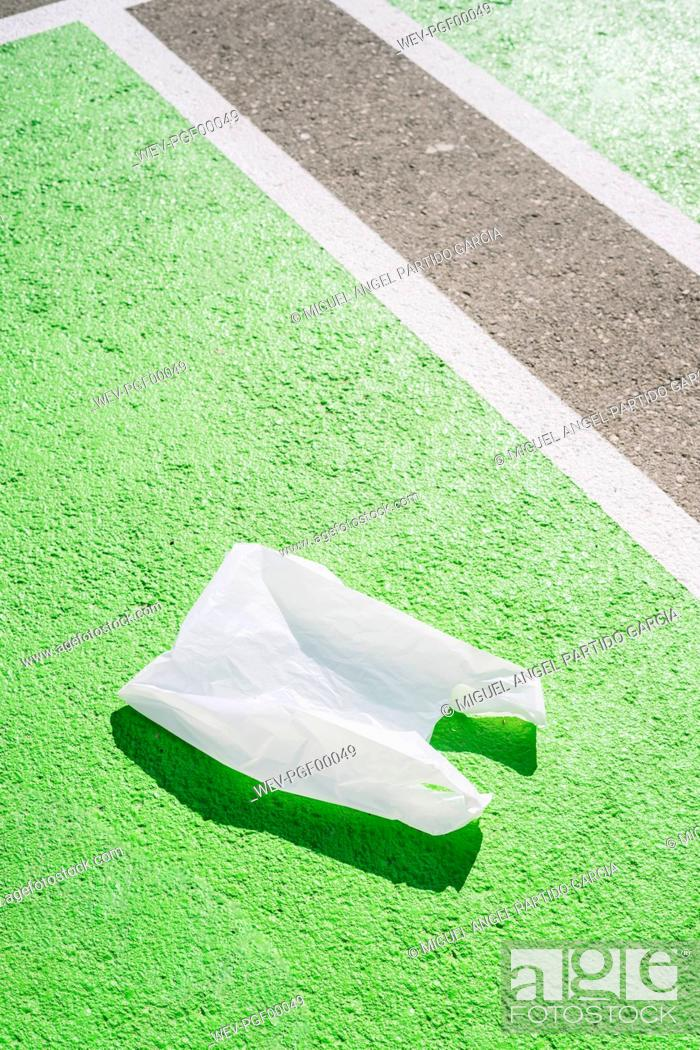 Stock Photo: Plastic bag on green footpath during sunny day.