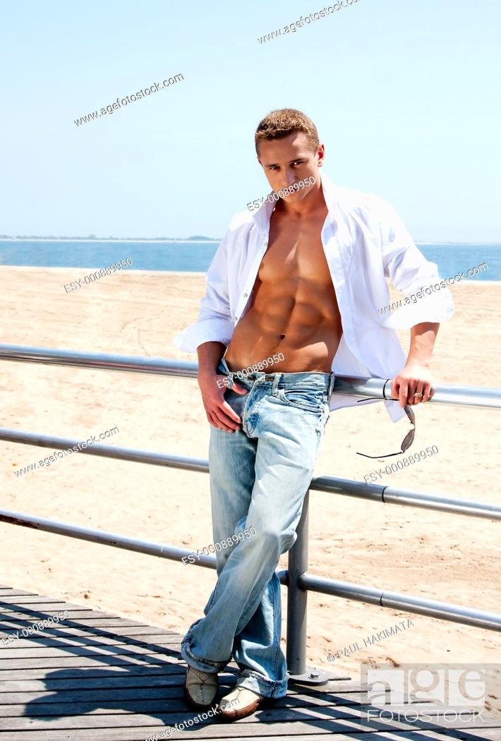 Stock Photo: Sexy handsome male with sunglasses and toned body showing six pack abs with white shirt opne while standing next to railing on boardwalk at beach.