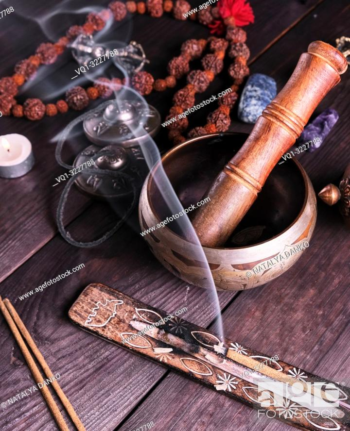 Imagen: copper singing bowl and a wooden stick on a brown table, a stick with incense is burning nearby.