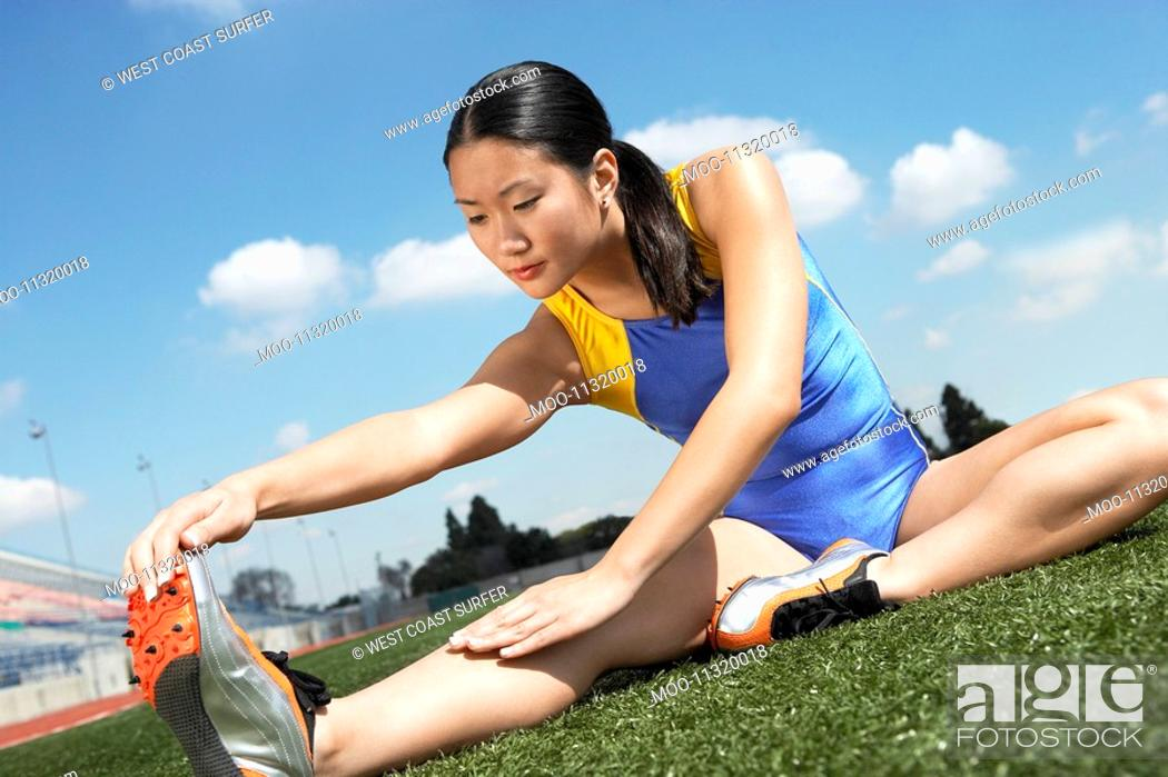 Stock Photo: Female athlete stretching on field.