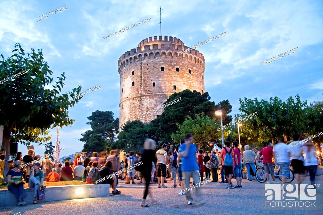Stock Photo: a busy evening at the illuminated white tower, symbol of the town of Thessaloniki, Macedonia, Greece.