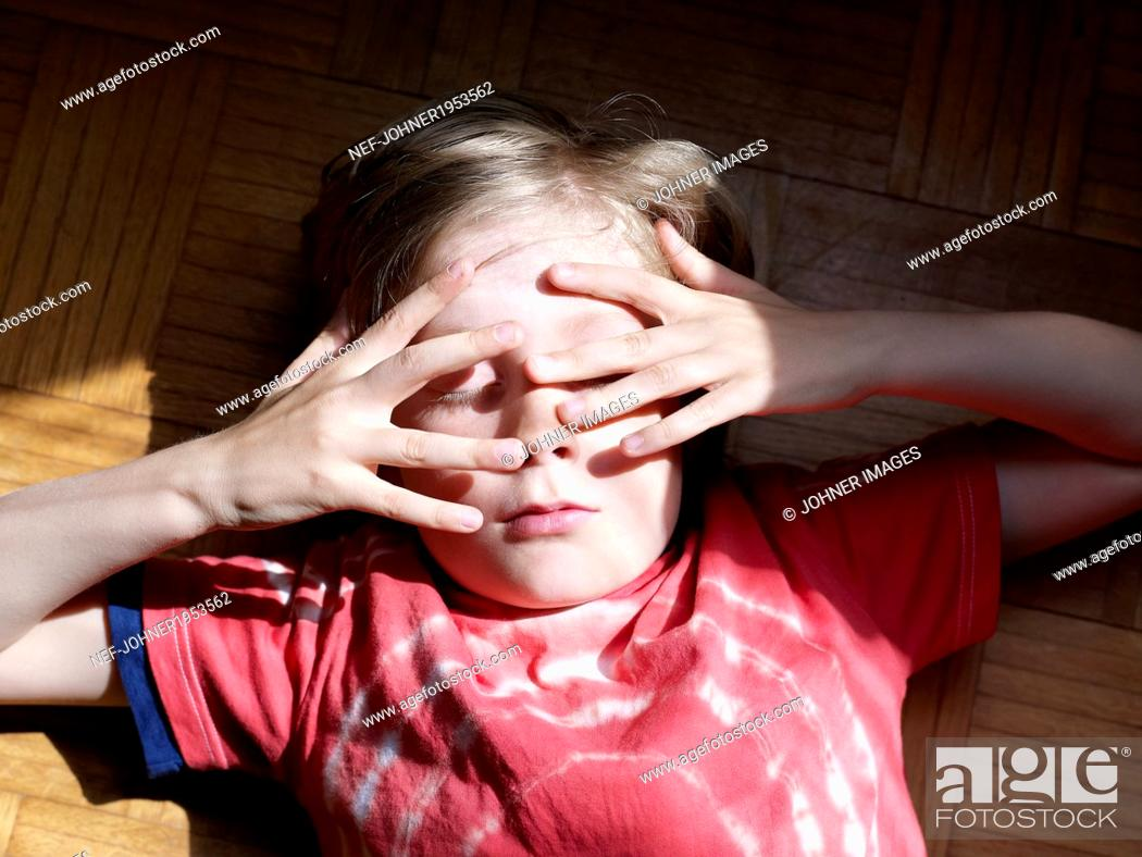 Stock Photo: Boy covering his face, Stockholm, Sweden.