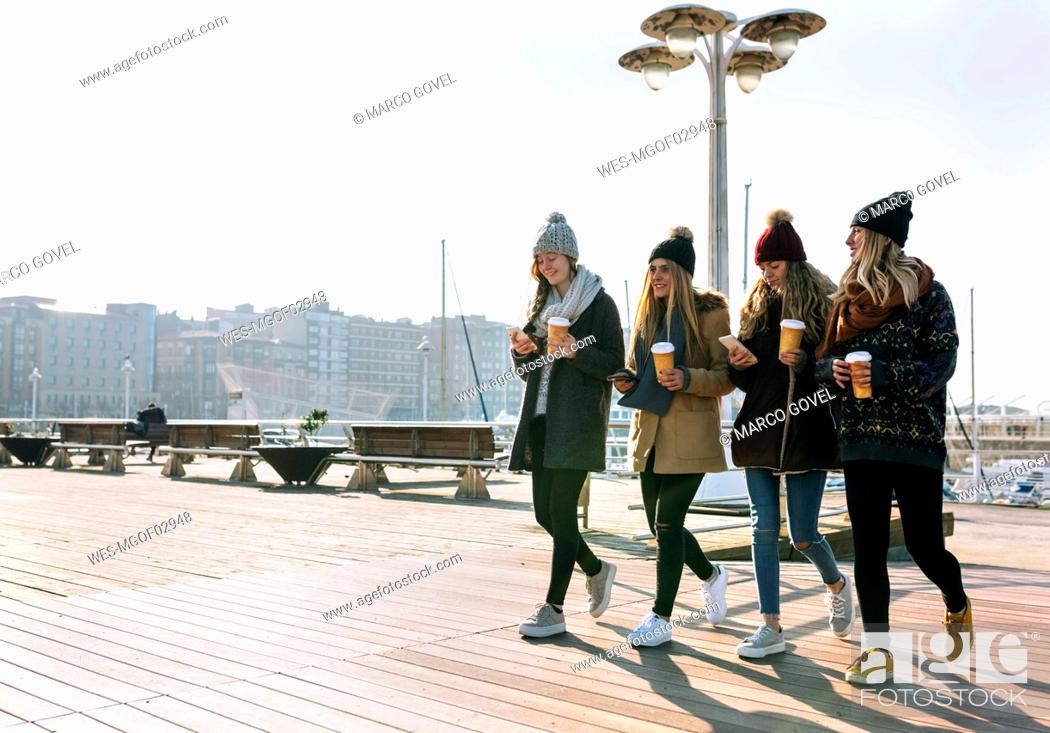 Stock Photo: Four friends with coffee to go and cell phones walking on promenade in winter.
