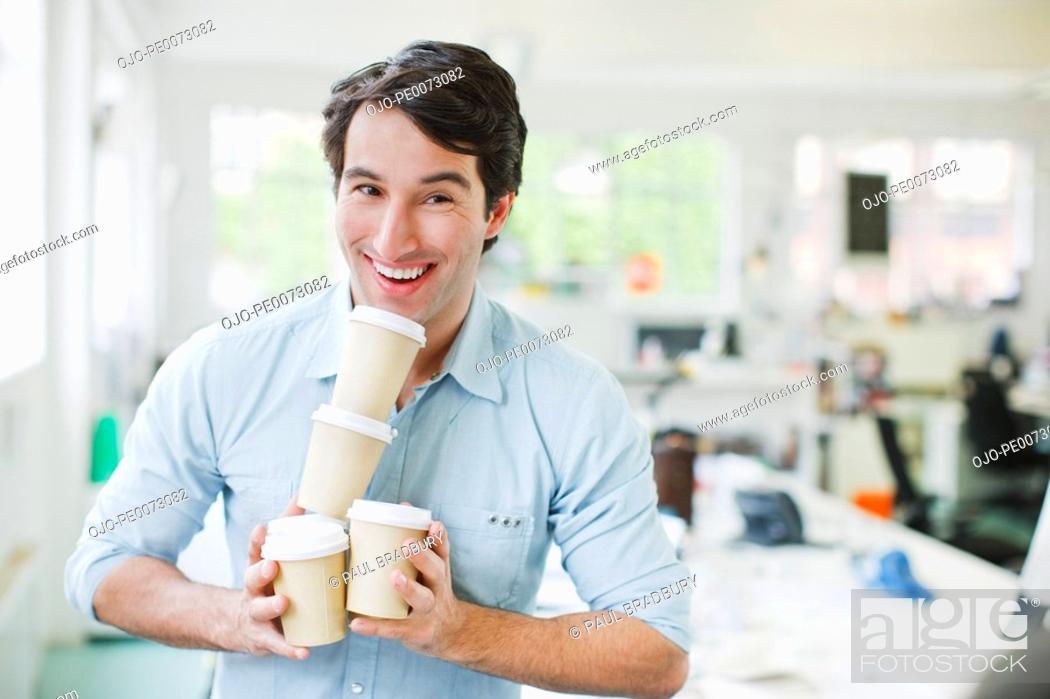 Stock Photo: Smiling businessman balancing coffee cups.