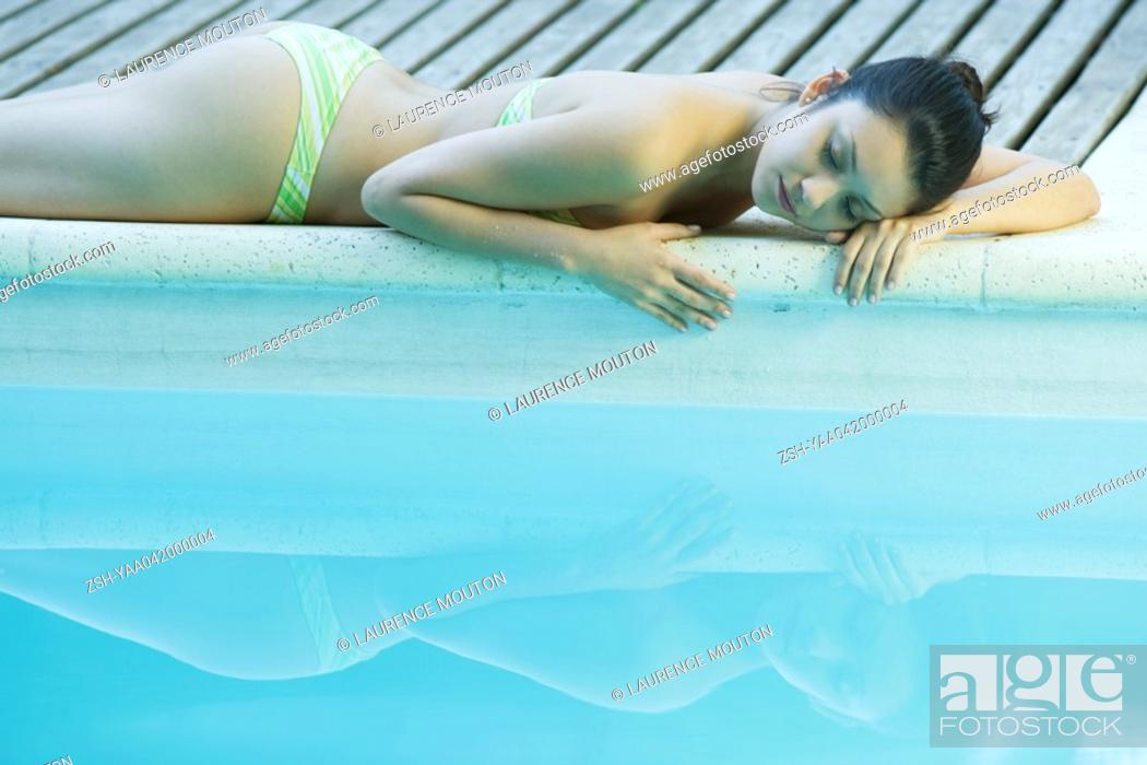 Stock Photo: Young woman lying next to pool.