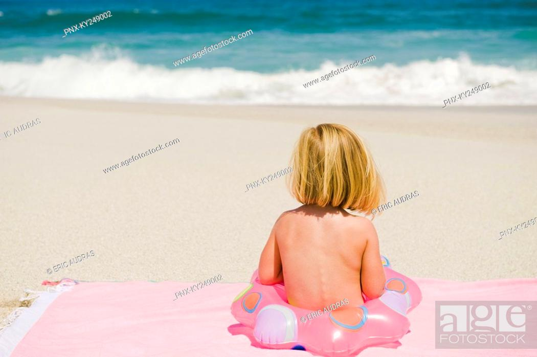 Stock Photo: Girl sitting with an inflatable ring on the beach.