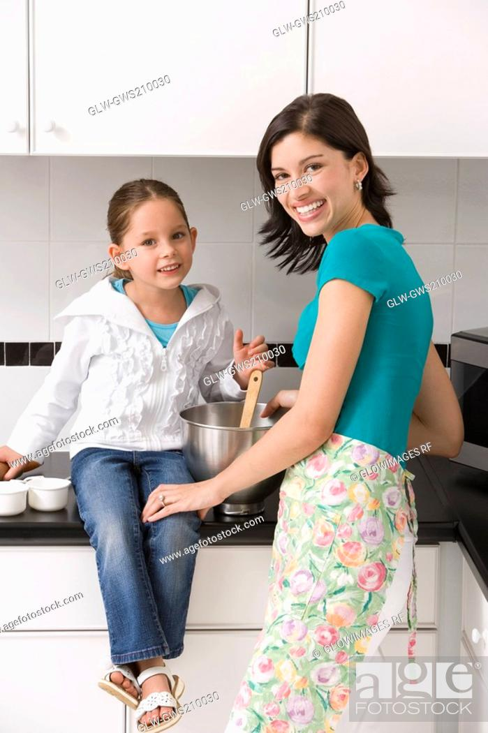 Stock Photo: Portrait of a young woman smiling with her daughter in a kitchen.