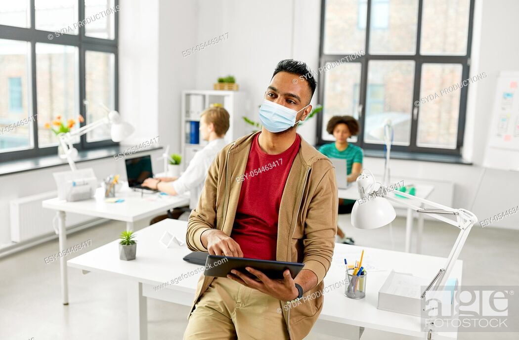 Stock Photo: indian man with tablet pc in face mask at office.