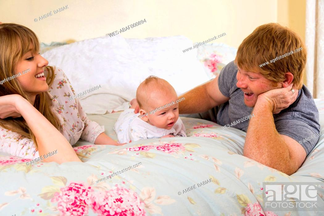 Stock Photo: Parents with baby boy on bed, smiling.