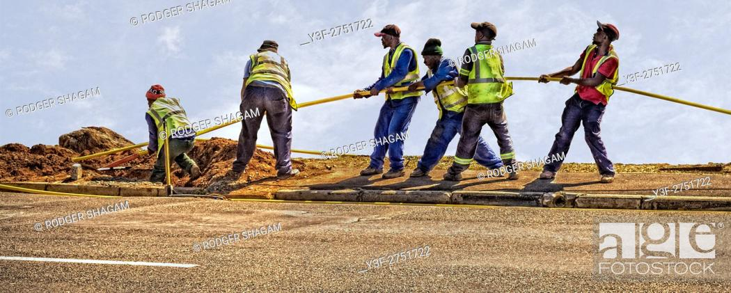 Stock Photo: A team of men working. Pulling through fibre optic cable connection. Cape Town, South Africa.