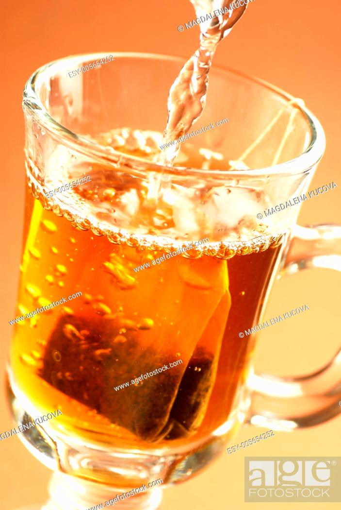 Photo de stock: Glass of tea with teabag and pouring water.