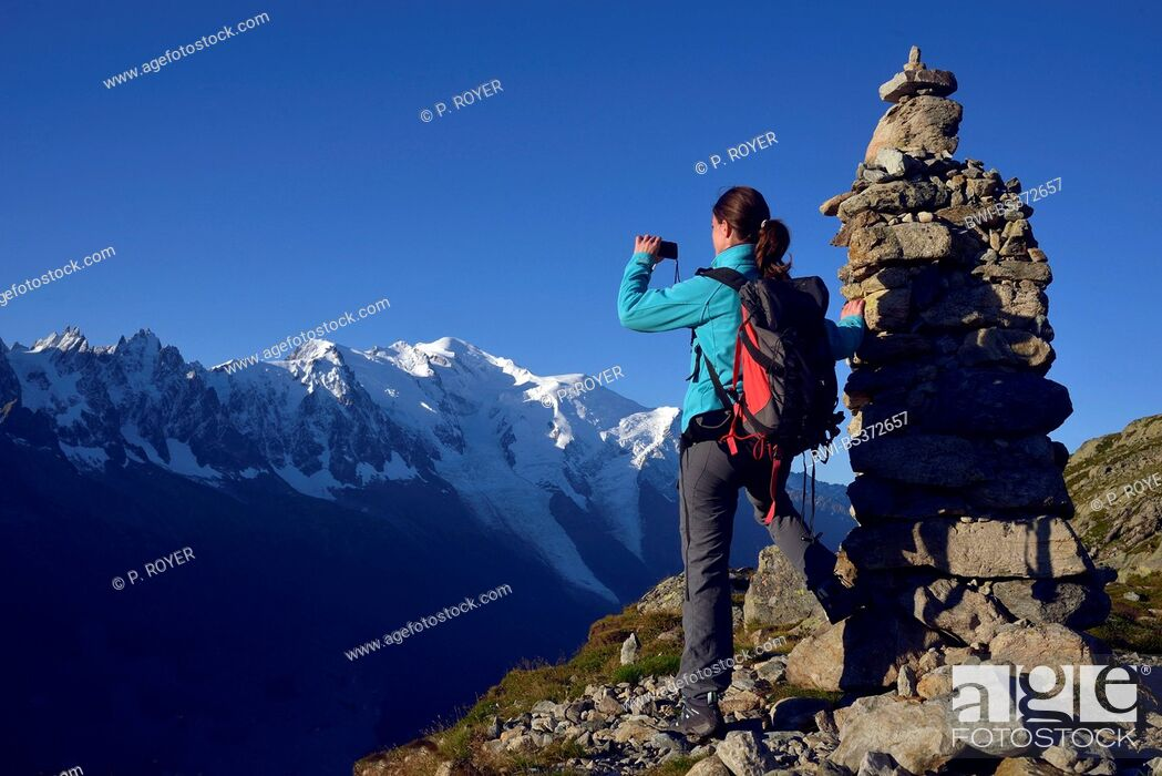 Imagen: female mountain hiker taking a picture next ot a pile of stones in front of Mont Blanc, the highest summit of Europa, France, Haute-Savoie.
