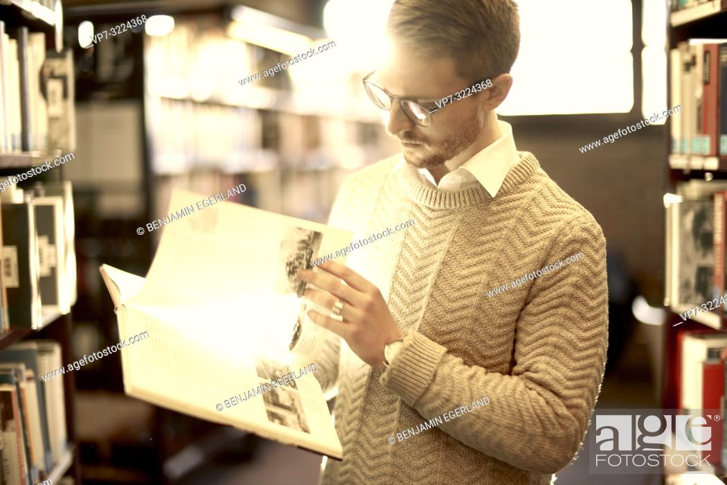 Stock Photo: man browsing book, library, glasses, student, university, knowledge.