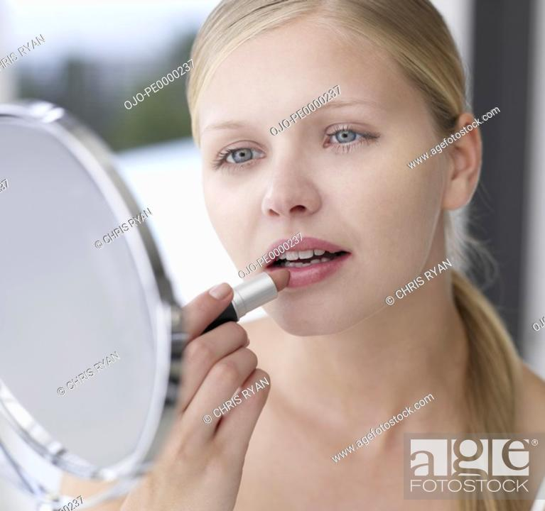 Stock Photo: Woman applying lipstick in mirror.