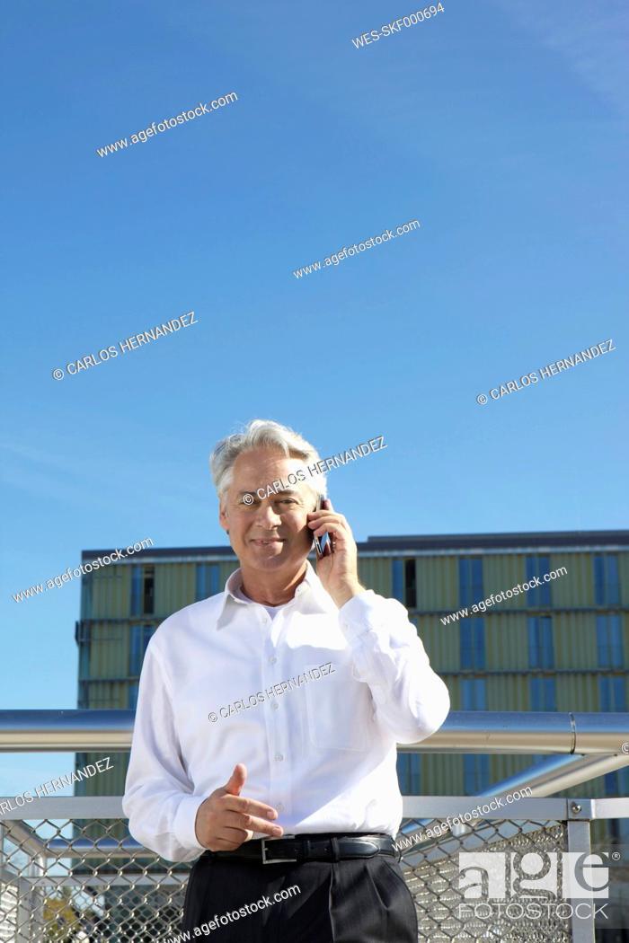 Stock Photo: Germany, Bavaria, Munich,Businessman talking on phone, smiling, portrait.