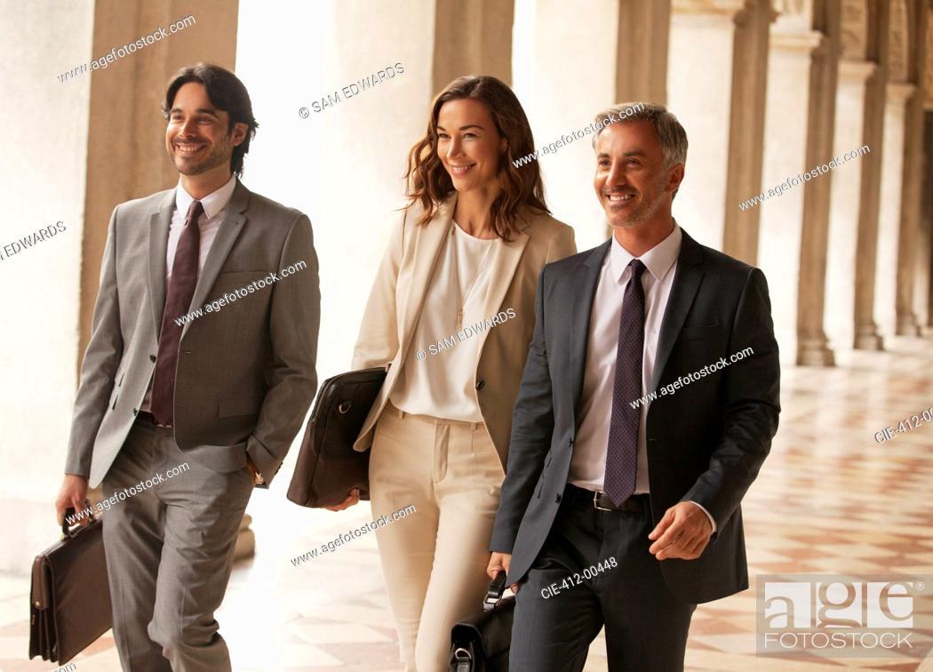 Stock Photo: Smiling business people walking along corridor.