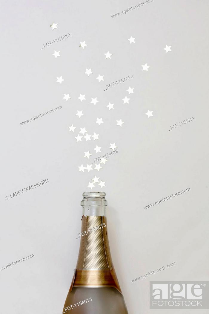 Stock Photo: Star shaped confetti spraying out of a champagne bottle.