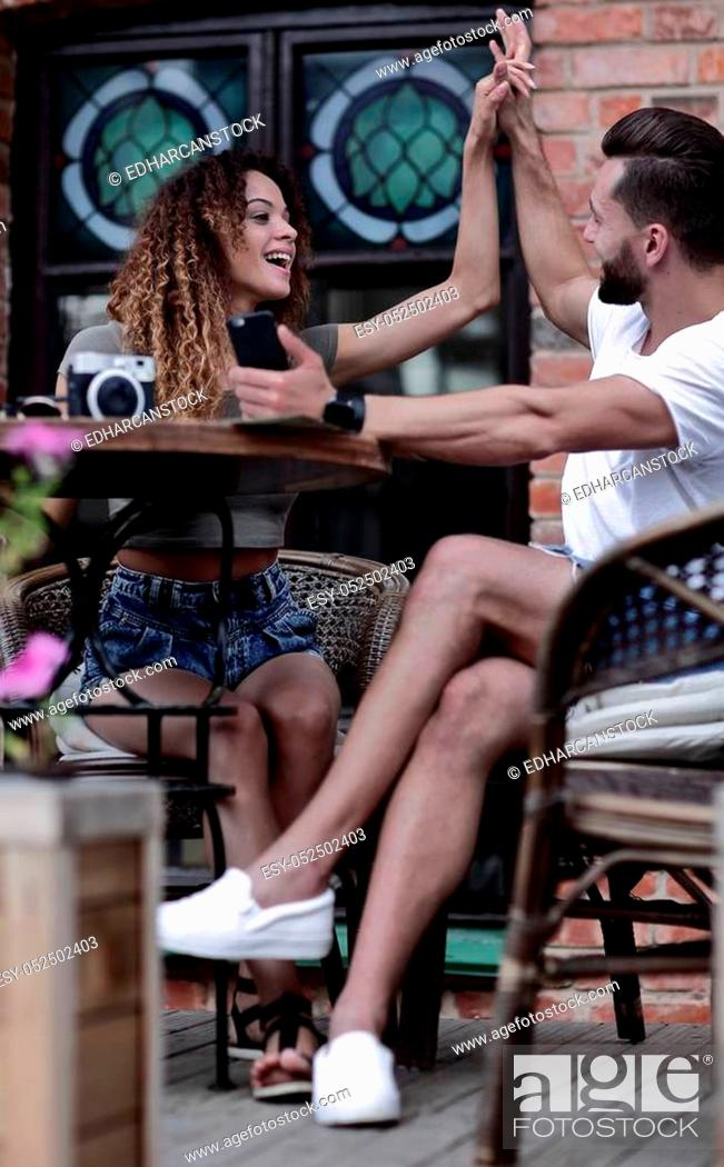 Stock Photo: Portrait of a young couple sitting down at a cafe outside.