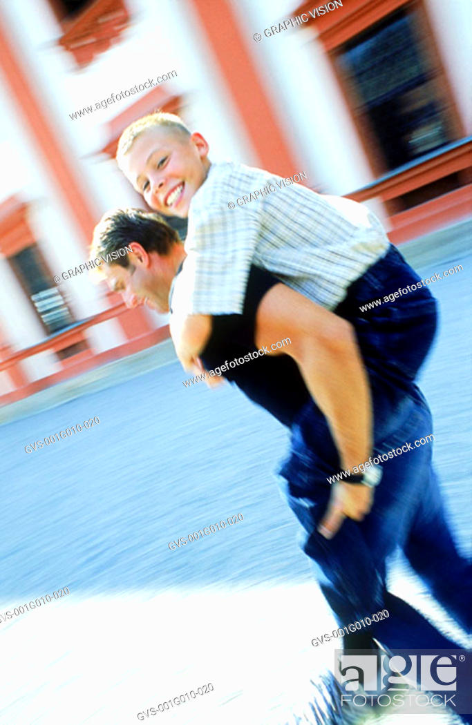 Stock Photo: Blurred side profile of a man carrying a boy on his back.