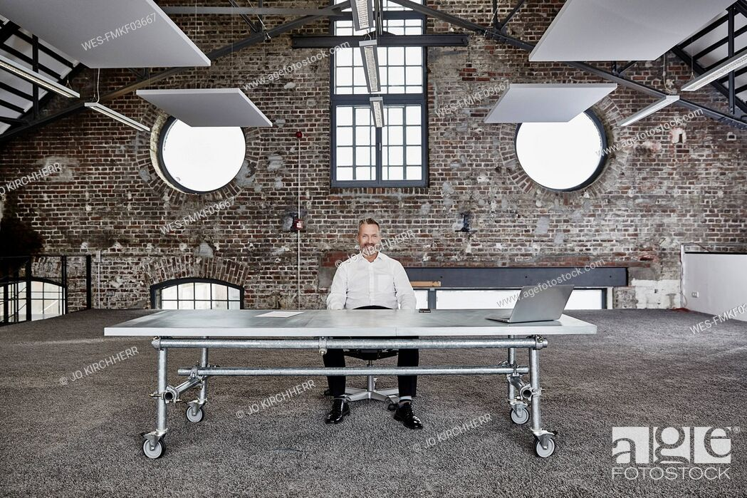 Stock Photo: Portrait of confident businessman sitting at rolling table in a loft.
