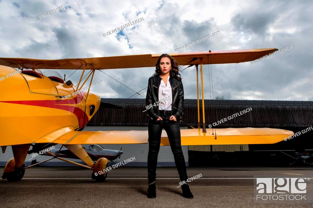 Stock Photo: Young woman with leather jacket poses with yellow double-decker aviator, fashion.