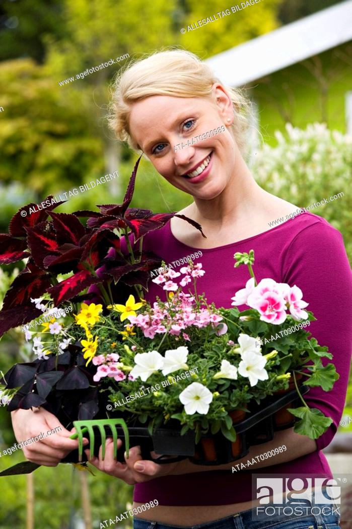 Stock Photo: Woman holding a range of different flower pots.