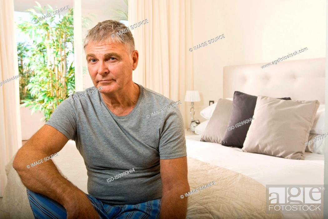 Stock Photo: Senior man sitting on bed.